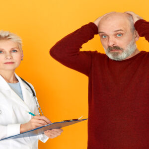 Isolated image of shocked unshaven senior man holding hands on his bald head being diagnosed with diabetes during medical consultation with mature female doctor. Health, sickness and treatment