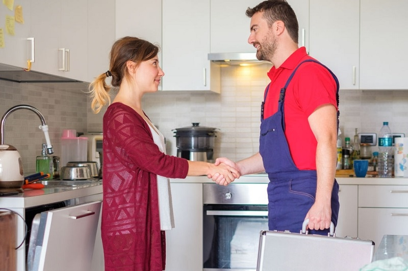 Satisfied housewife handshaking after plumber quick service